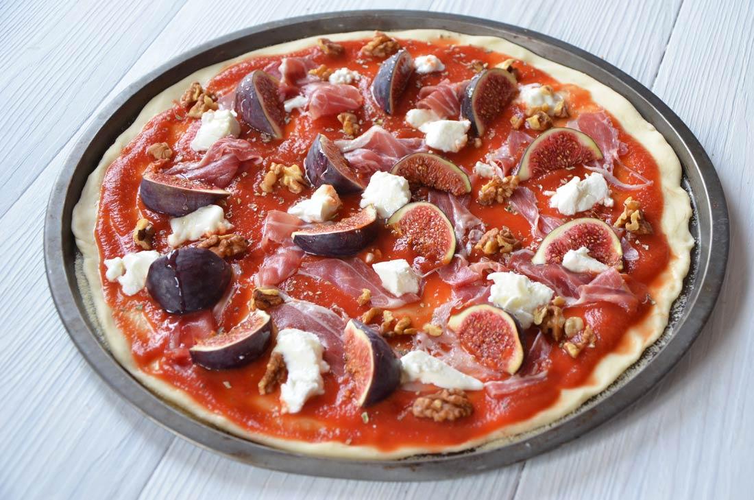 Pizza chèvre jambon cru figues et noix avant cuisson